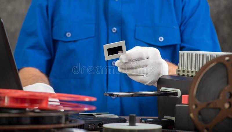 Technik z bia?ymi r?kawiczkami digitizing starego 35mm ekranowego obruszenie zdjęcia royalty free