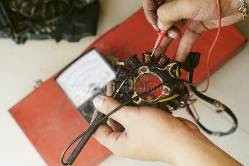 Technika mienie, czek magnesowa motorowa zwitka, generatorowa zwitka hulajnoga i motocykl z multimeter przy motocyklu garażem, obrazy stock