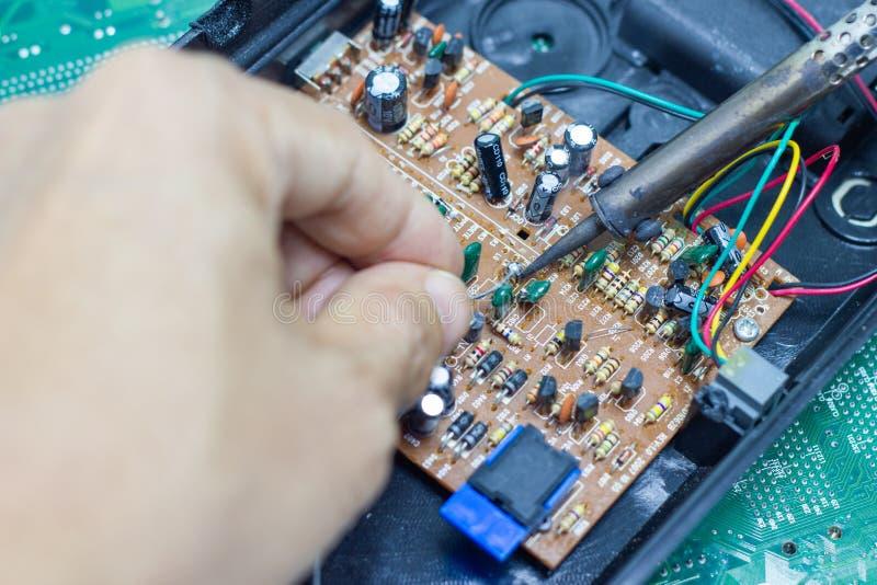 Technika naprawiać elektroniczny komputerowego obwodu deska lutowniczymi żelazami obraz stock