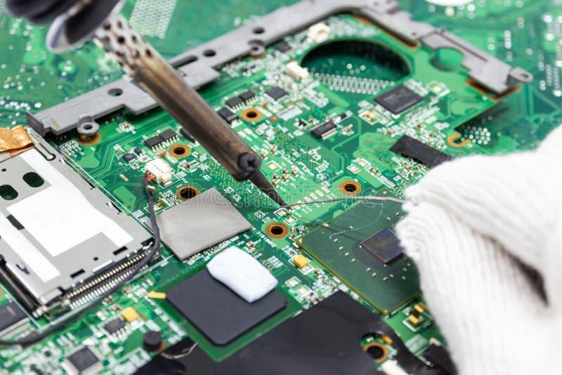 Technika naprawiać elektroniczny komputerowa ` s obwodu deska lutowniczymi żelazami obraz royalty free