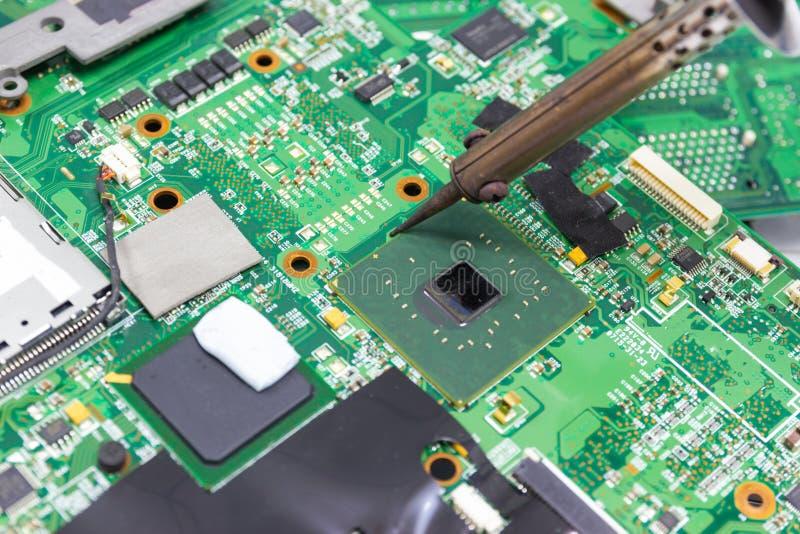 Technika naprawiać elektroniczny komputerowa ` s obwodu deska lutowniczymi żelazami obrazy stock