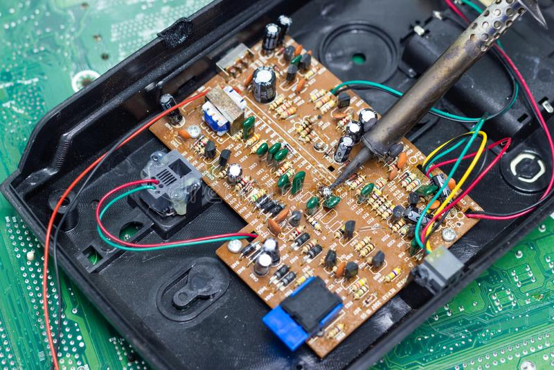 Technika naprawiać elektroniczny komputerowa ` s obwodu deska lutowniczymi żelazami zdjęcie royalty free