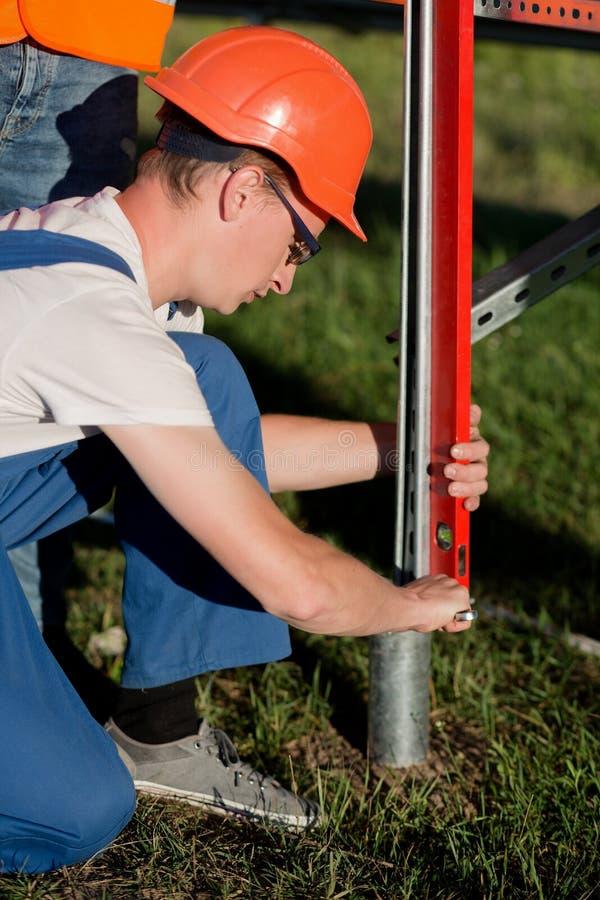 Techniker beschäftigt mit Installation von Stapel der schraubenartigen Schraube für Sonnenkollektoren stockfoto