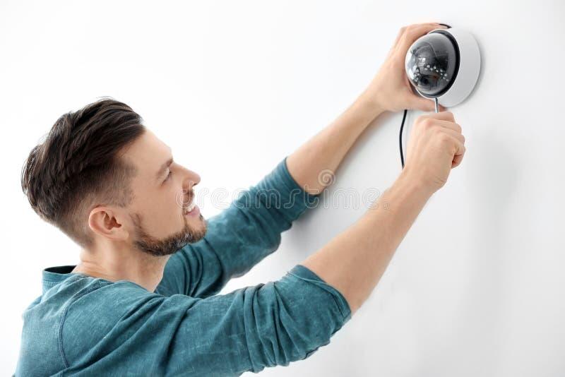 Techniker, der Überwachungskamera auf Wand installiert lizenzfreie stockbilder