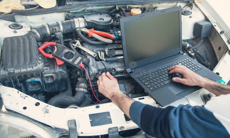 Techniker, der Automotor mit einem Anwendungslaptop ?berpr?ft stockfoto