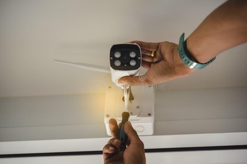 Techniker, der drahtlose Überwachungskamera installiert, durch geschraubt für Hauptsicherheitssystem und installiertes w lizenzfreie stockbilder