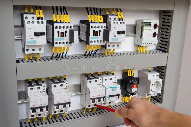 Techniker, der am elektrischen Kabinett arbeitet stockfotografie