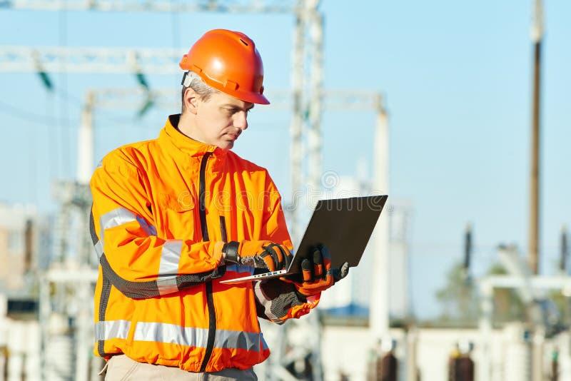 Techniker, der mit Laptop an Notfall des elektrischen Stroms der Hitze arbeitet stockbilder