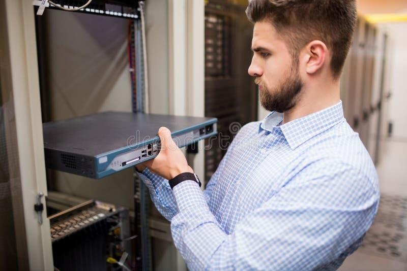 Techniker, der Server von Gestell angebrachtem Server entfernt lizenzfreie stockfotos