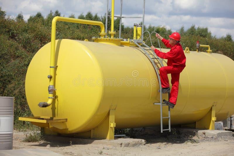 Techniker in der Uniform, die auf großem Kraftstofftank klettert lizenzfreies stockfoto