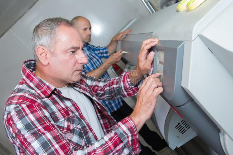 Techniker, die große Tintenstrahldrucker überprüfen lizenzfreies stockbild