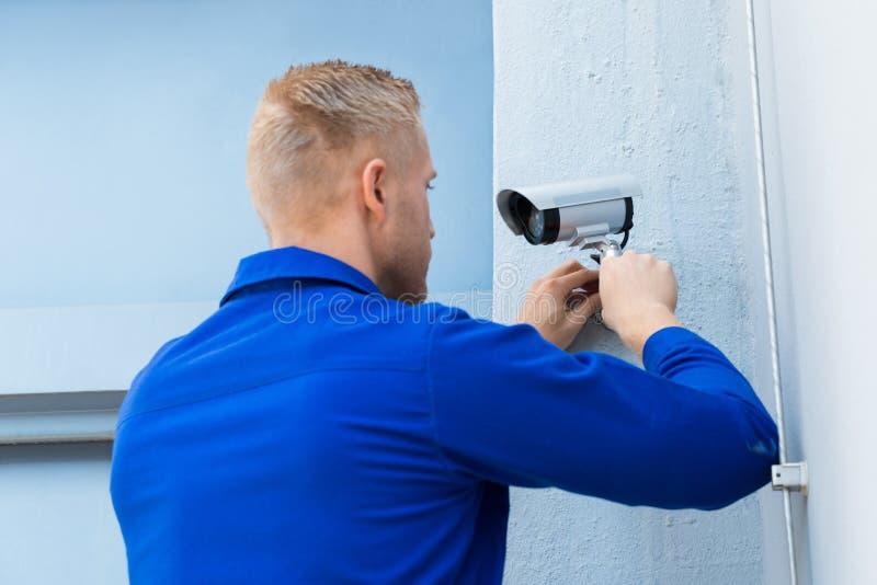 Techniker-Installing Camera In-Ecke stockfotos