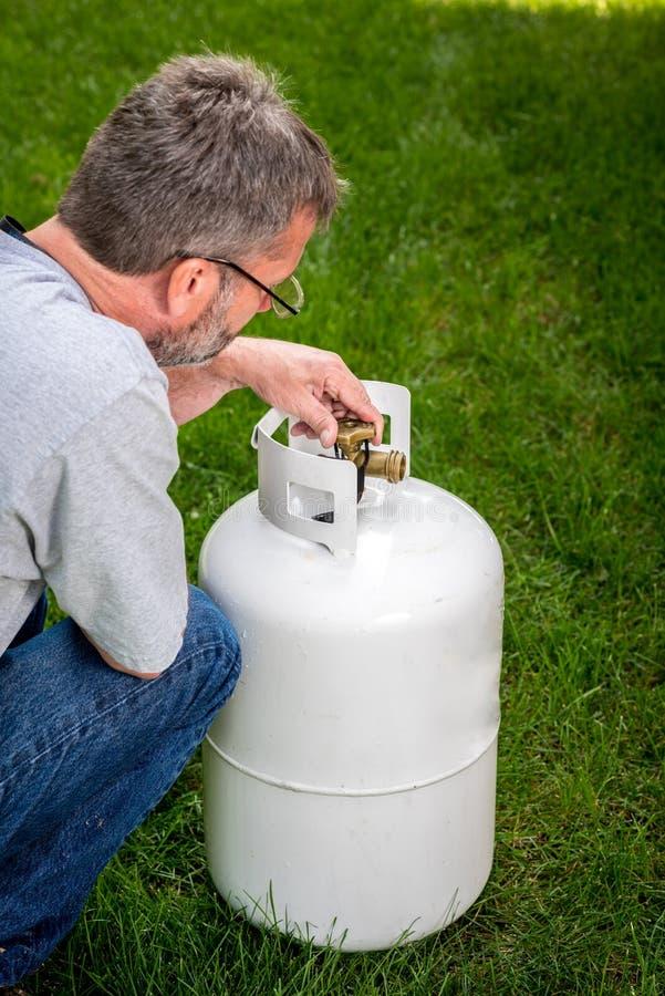 Techniker kontrolliert das Ventil auf einem Propantank lizenzfreie stockbilder