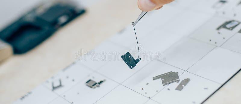 Techniker mit Pinzette trägt Teile des Handys während Se lizenzfreie stockfotos