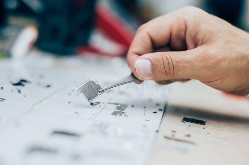 Techniker mit Pinzette trägt Teile des Handys während Se lizenzfreies stockfoto