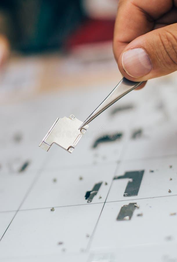 Techniker mit Pinzette trägt Teile des Handys während Se lizenzfreies stockbild
