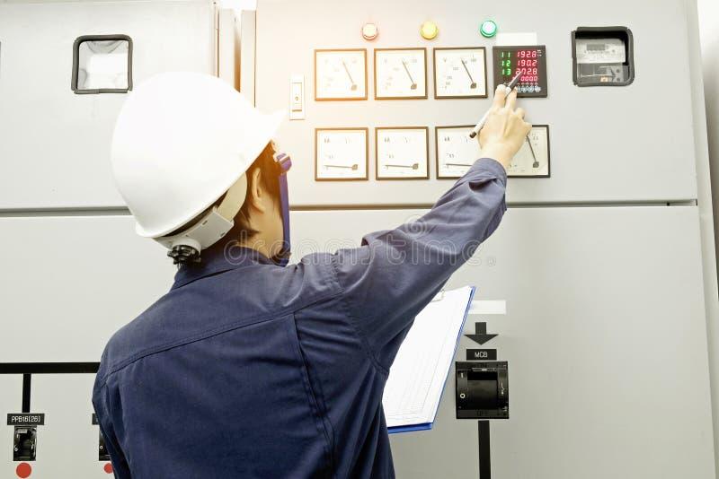Techniker notiert Datenspannung oder -strom im Bedienfeld lizenzfreies stockfoto