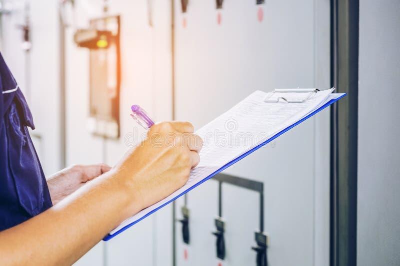 Techniker notiert Datenspannung oder -strom im Bedienfeld lizenzfreie stockbilder