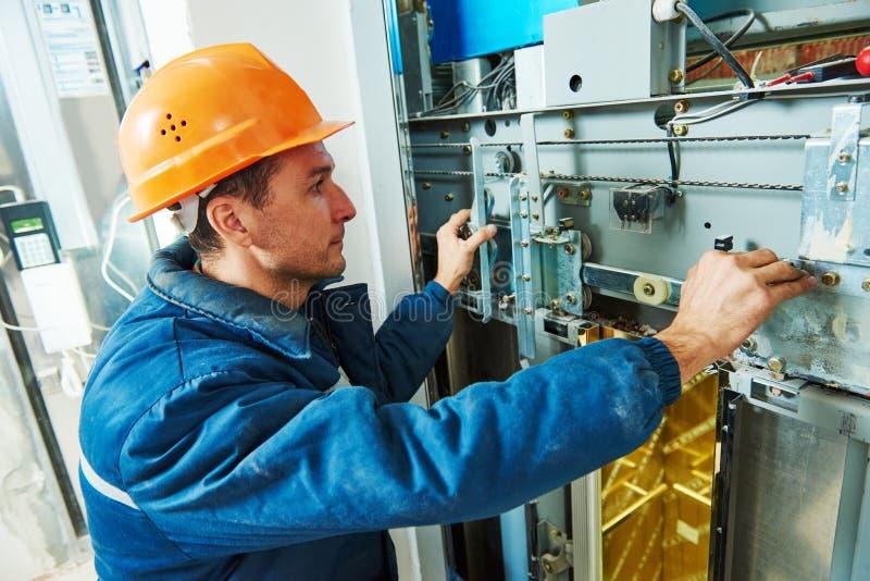 Technikerarbeitskraft, die Aufzugsmechanismus des Aufzugs justiert lizenzfreie stockfotos