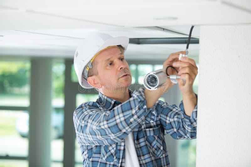 Technikerarbeitskraft, die Videoüberwachungskamera auf Wand installiert lizenzfreies stockfoto
