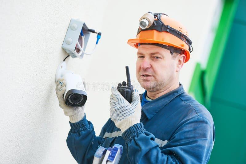 Technikerarbeitskraft, die Videoüberwachungskamera auf Wand installiert lizenzfreies stockbild