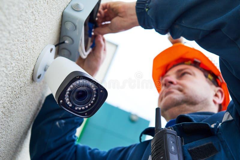 Technikerarbeitskraft, die Videoüberwachungskamera auf Wand installiert lizenzfreie stockfotografie