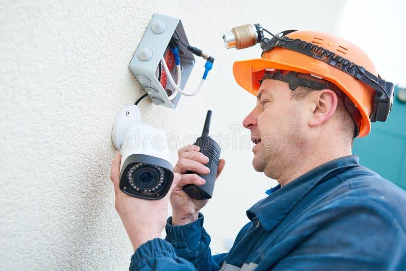 Technikerarbeitskraft, die Videoüberwachungskamera auf Wand installiert stockfotografie