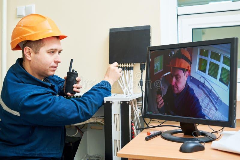 Technikerarbeitskraft, die Videoüberwachungssystem justiert stockfotografie