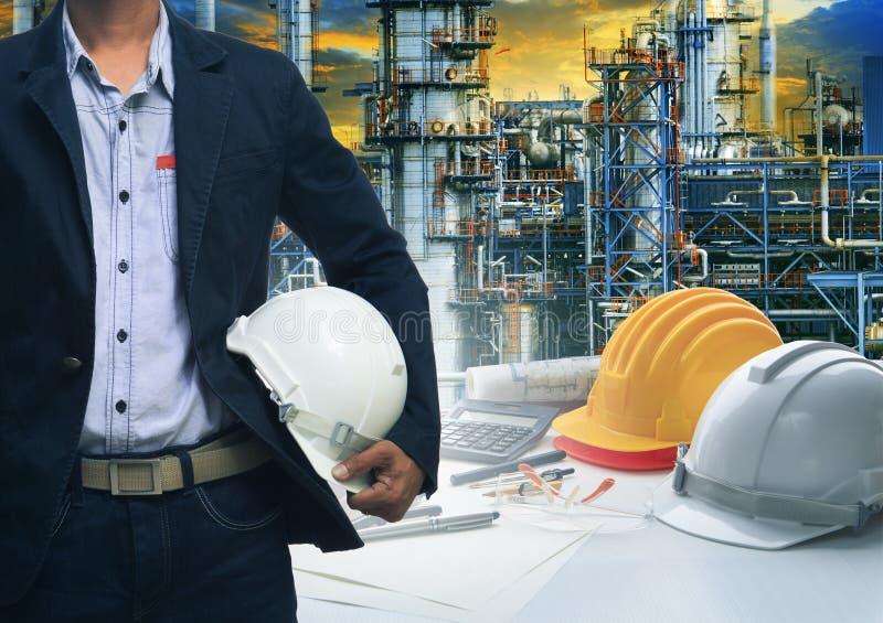 Technikmann, der mit weißem Schutzhelm gegen Öl r steht stockfotos