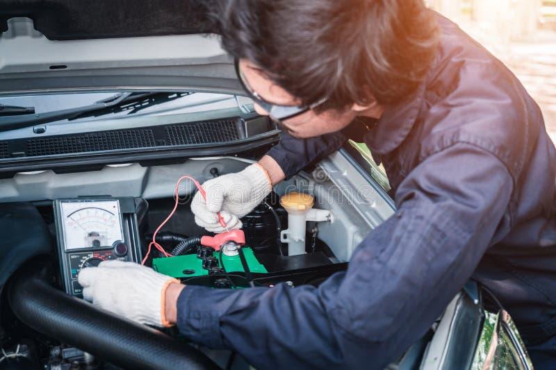 Technikschnittstelle gegen ?ndernde Autobatterie des Mechanikers lizenzfreie stockfotos