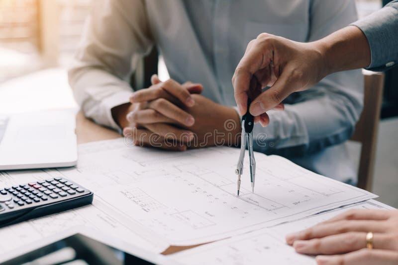Technikzusammenarbeiten zwei und Anwendung der digitalen Tablette, die Plan und Analyse mit Architekturplan auf Schreibtisch scha lizenzfreies stockbild