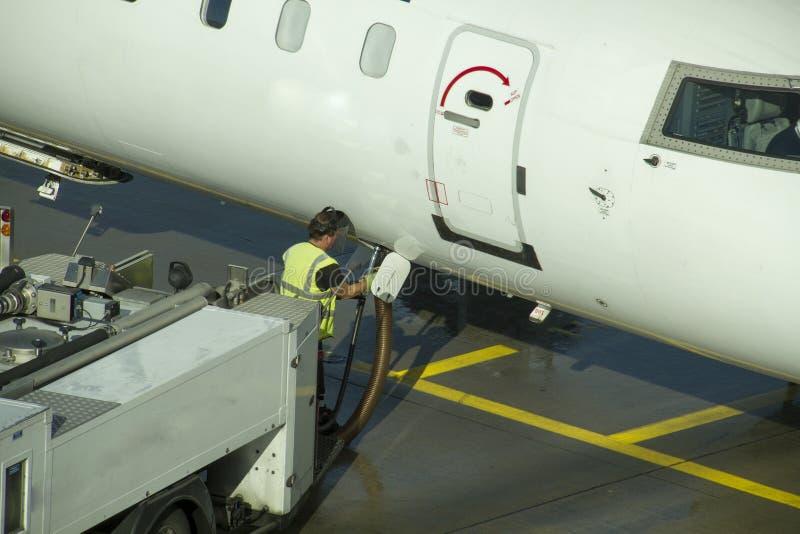 Technitian working below a passenger airplane. stock photography