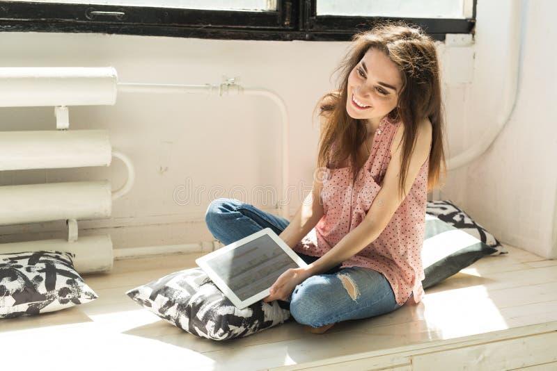 Technologia i ludzie pojęć - młoda studencka kobieta używa pastylkę w domu fotografia royalty free