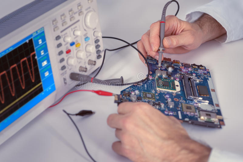 Technological background with closeup on tech hands. Technological background with closeup on tester checking motherboard. Toned image. Shallow DOF, exact focus royalty free stock photography