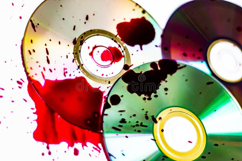 Technological background created with the photo of three wet CDs, the light accentuates the reflections coloring them.  stock photography
