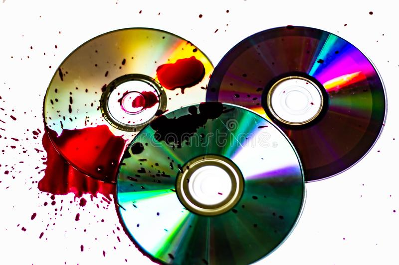 Technological background created with the photo of three wet CDs, the light accentuates the reflections coloring them.  stock images
