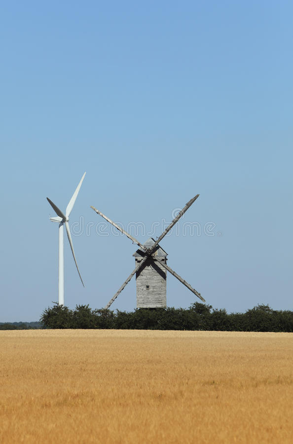 Technological contrast. Image of a traditional windmill close to a modern eolian turbine in a cereal field stock image