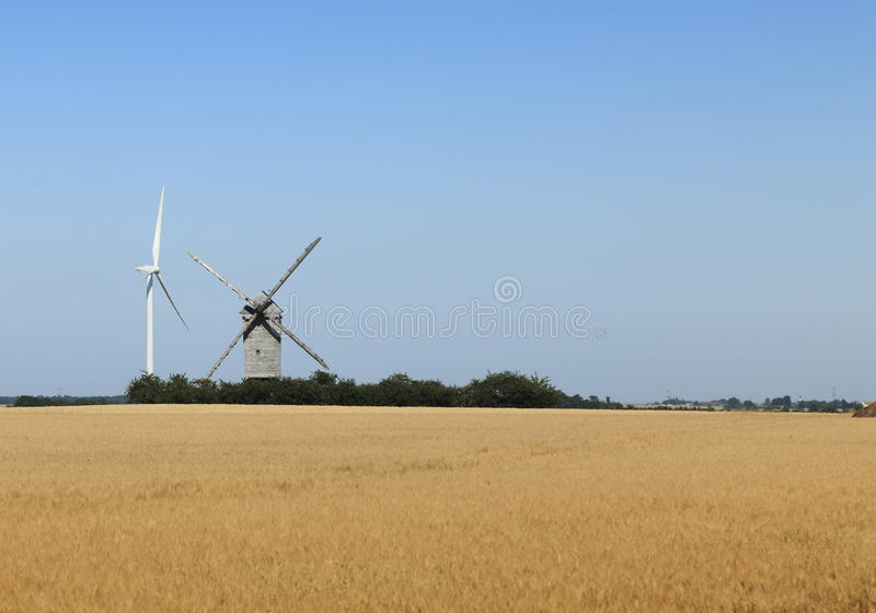 Technological contrast. Image of a traditional windmill close to a modern eolian turbine in a cereal field royalty free stock photos