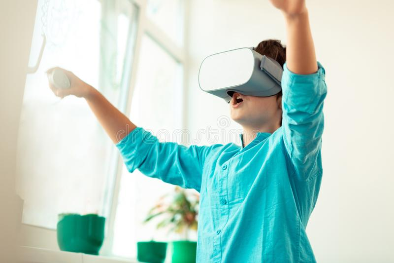 Excited schoolboy playing virtual games in the classroom. royalty free stock photos