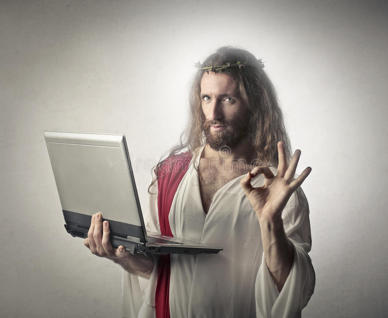 Technological Jesus. Holding a laptop royalty free stock image