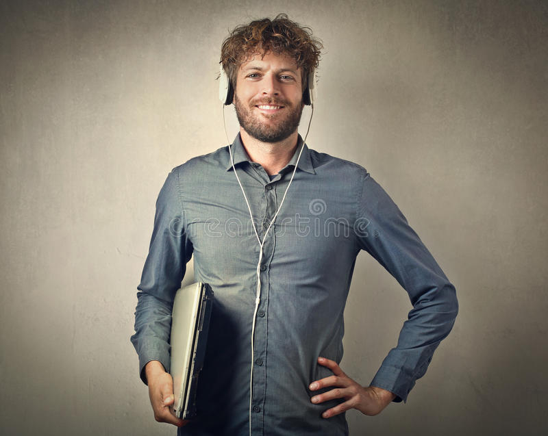 Technological man. Listening to music and carrying a computer royalty free stock image