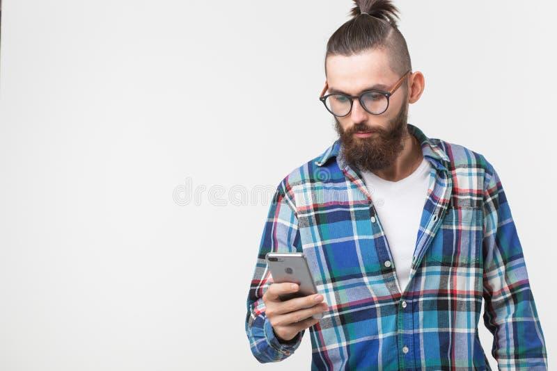 Technologieën, manier en mensenconcept - Koele mens met baard die telefoon over witte achtergrond met exemplaarruimte met behulp  stock fotografie