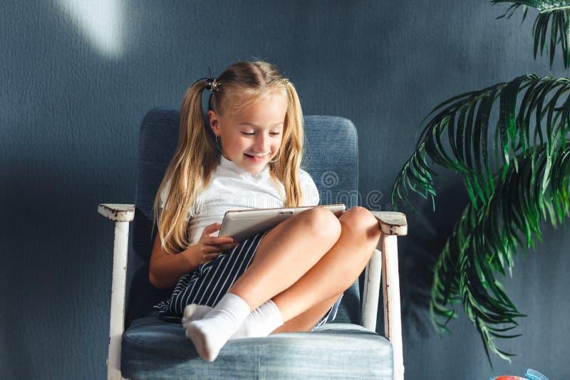Technologieën, mensenconcept - jonge blondy meisjeszitting op een stoel en het letten van de op tablet of het surfen van netto en stock foto