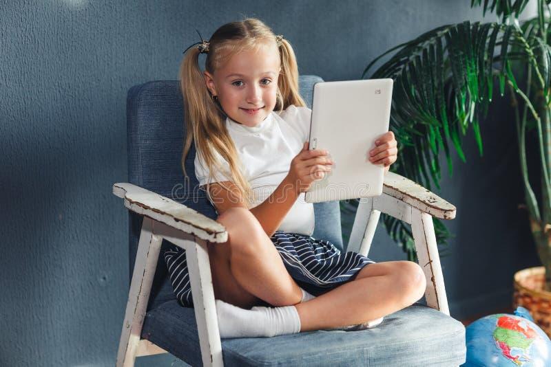 Technologieën, mensenconcept - jonge blondy meisjeszitting op een stoel en het letten van de op tablet of het surfen van netto en royalty-vrije stock foto's
