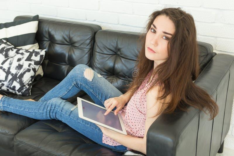 Technologieën, mensenconcept - jonge vrouwenzitting op bank en het letten van op laptop of het surfen van het net royalty-vrije stock foto