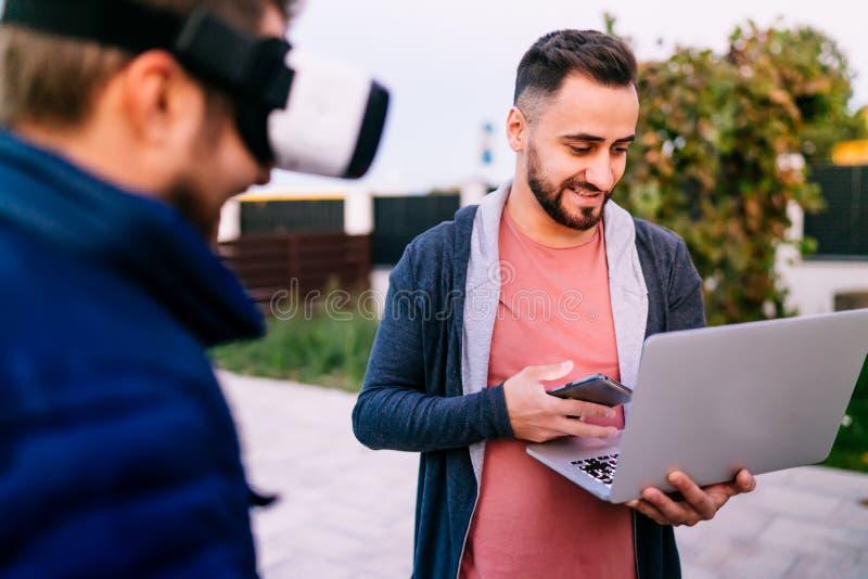 technologieën - moderne levensstijl met twee ontwikkelaars die aan nieuwe apps voor virtuele werkelijkheidsbeschermende brillen w royalty-vrije stock afbeeldingen