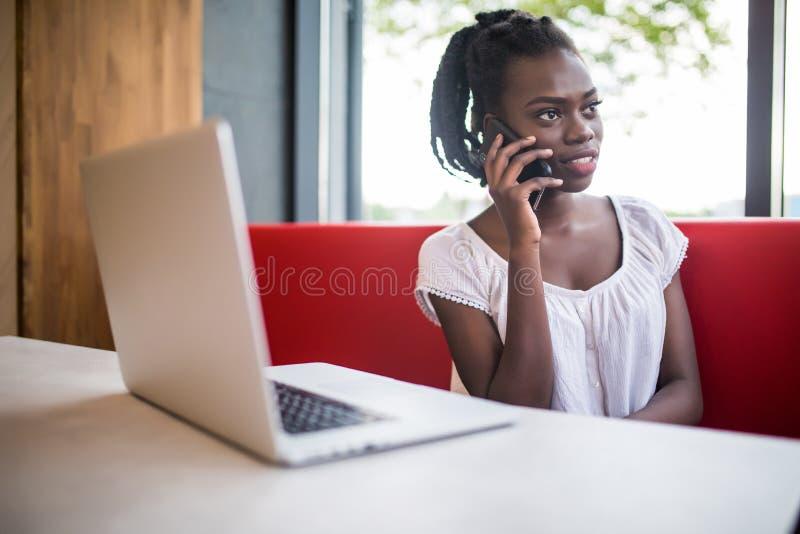 Technologie en communicatie concept Succesvolle Afrikaanse Amerikaanse onderneemster met Afro-kapsel die telefoongesprekken met s stock afbeelding