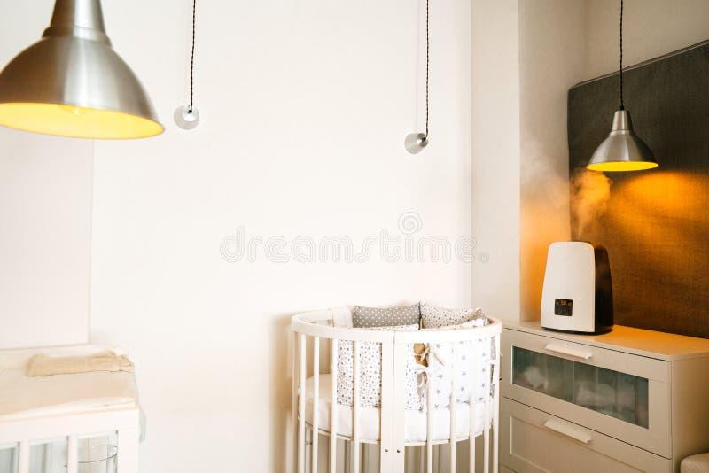 Technologie en gezondheid Stoomluchtbevochtiger in de kinderenslaapkamer naast het pasgeboren babybed in een modieus licht binnen royalty-vrije stock afbeeldingen