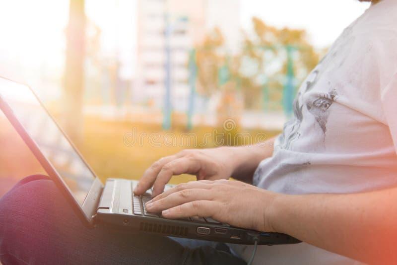Technologie en mededeling, het werk bij het toetsenbord met laptop in openlucht, stock afbeelding