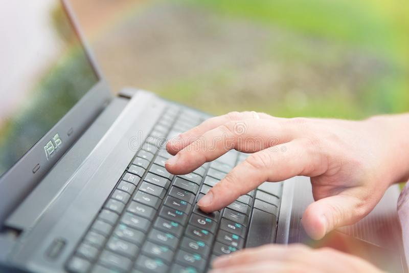 Technologie en mededeling, het werk bij het toetsenbord met laptop in openlucht, stock fotografie